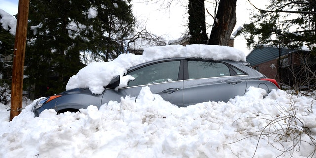 A car sits buried in snow from the blizzard on 9th Street in Boulder, Colo. on Thursday.