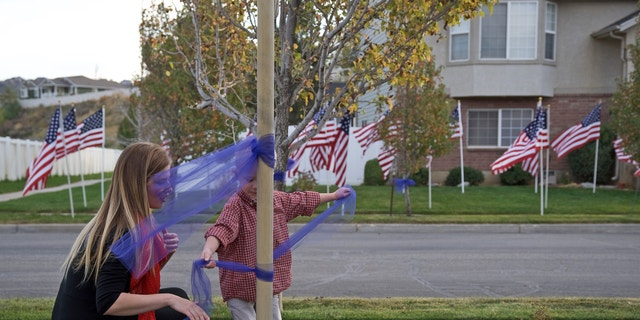 Kimberlee Jensen places a blue ribbon around a flag pole with her son last week across the street from Officer Cody Brotherson's home.