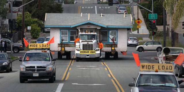 In this photo taken Monday, March 28, 2016, workers oversee the hauling of a small home in Hillcrest, Calif., as it left the plot of land on the corner of Vermont Street and is moving east along Howard Avenue. The home, built in 1925, was being moved to a storage yard in Otay Mesa, Calif., before finally being relocated to a new lot in Chula Vista, Calif. The owner, Anne Wilson, had lived in the 800-square-foot stucco home for 23 years, plans to build a new three-story home on the lot.  (Peggy Peattie/The San Diego Union-Tribune via AP)  NO SALES; MANDATORY CREDIT