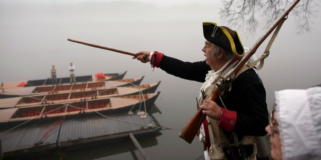 Revolutionary War re-enactor Bill Strunk points his cane towards New Jersey as fog covers the river before the re-enactment of Washington crossing the Delaware River, Friday, Dec. 25, 2015, in Washington Crossing, Pa.  (AP Photo/ Joseph Kaczmarek)