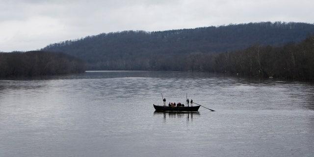 A group of Revolutionary War re-enactors row a Durham boat during the re-enactment of Washington crossing the Delaware River, Friday, Dec. 25, 2015, in Washington Crossing, Pa.  (AP Photo/ Joseph Kaczmarek)