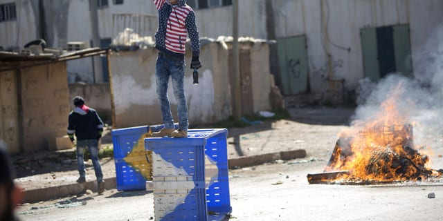 A Palestinian protester stands on top of a barricade during clashes with the Israeli military in the West Bank village of Kabatiya Thursday.