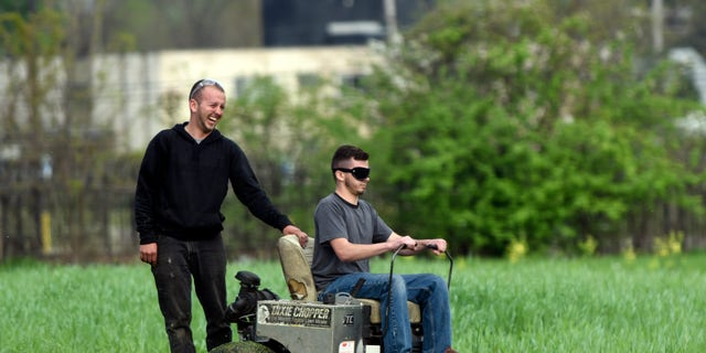 In this photo taken Wednesday May 11, 2016, Detroit Mower Gang members Gage Vaneckoute, left, of Bellville, Mich., laughs at the path his brother Chase has taken during a blindfolded mower contest at Hammerberg Field on Detroit's west side. The volunteers helping to maintain Detroit parks and playgrounds took a crack at mowing grass while blindfolded as part of a friendly competition. (Steve Perez/Detroit News via AP)  DETROIT FREE PRESS OUT; HUFFINGTON POST OUT; MANDATORY CREDIT