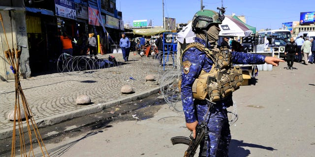 A federal policeman stands guard at the scene of a suicide bombing in Baghdad's Tayaran Square.