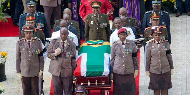 A military honor guard carries anti-apartheid activist Winnie Madikizela-Mandela's coffin, wrapped in the flag of South Africa, out of Orlando stadium following her funeral service, in Soweto, South Africa, Saturday, April 14, 2018.