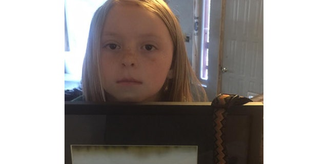 Helfrieck's 8-year-old daughter holds a photo of the family's dog, Abby, killed March 12 by an M-44 in Wyoming.