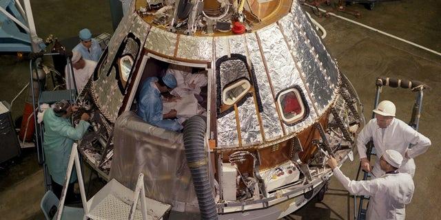 Technicians work on an Apollo command module in 1966.