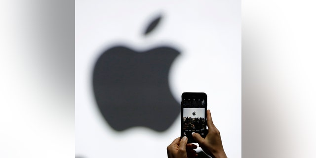 FILE - In this Monday, June 5, 2017, file photo, a person takes a photo of an Apple logo before an announcement of new products at the Apple Worldwide Developers Conference in San Jose, Calif. Apple is expected to demand $1,000 for the fanciest iPhone that it has ever made, thrusting the market into a new financial frontier that will test how much consumers are willing to pay for a device that has become an indispensable part of modern life. (AP Photo/Marcio Jose Sanchez, File)