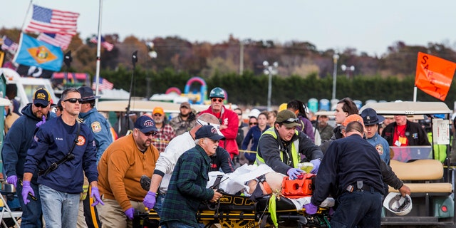 Paramedics transport a man to an ambulance after he was injured when an apparatus used to launch pumpkins into the air exploded at the World Championship Punkin Chunkin Contest in Bridgeville, Del., Sunday, Nov. 6, 2016.
