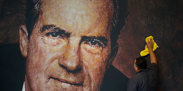 FILE -- In this Wednesday, Oct. 5, 2016 photo, Tayron Santos cleans the newly-installed wall mural of former President Richard Nixon in the lobby area of the Richard Nixon Presidential Library and Museum in Yorba Linda, Calif.