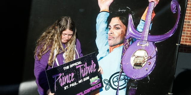 A Prince fan poses with a large photo backdrop of the late Prince as fans gather outside Xcel Arena Thursday, Oct. 13, 2016, in St. Paul, Minn., waiting for a concert honoring the musician who died in April of accidental painkiller overdose.