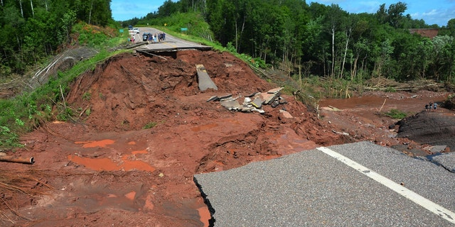 July 12, 2016: People observe part of Wisconsin Highway 13, washed out after heavy rains, south of Highbridge in Ashland, Wis.