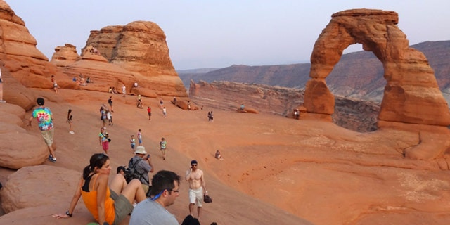 Tourists gather at the Arches National Park in Moab, Utah.