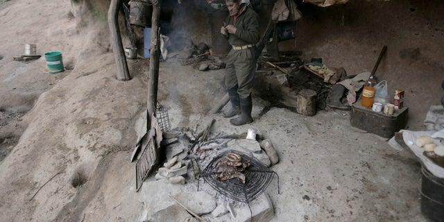 Pedro Lucas cooks sausage inside his mountain cavern.