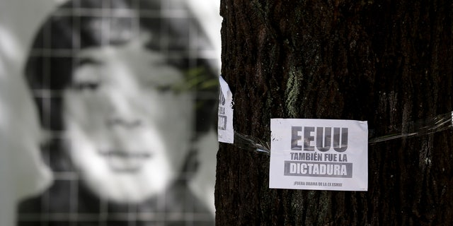 """March 16, 2016: A picture of a person that was disappeared during Argentina's military dictatorship is seen behind a leaflet on a tree that reads in Spanish """"The U.S. was also the dictatorship, Obama out of former Argentine Navy School of Mechanics"""" at the Space for Memory and for the Promotion and Defense of Human Rights in Buenos Aires. (AP Photo/Natacha Pisarenko)"""