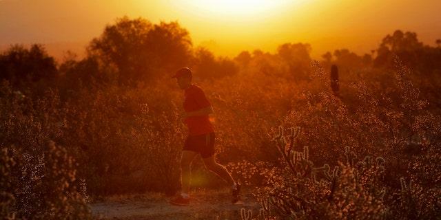 A man runs through the desert at sunrise, Friday, June 16, 2017, in Phoenix.