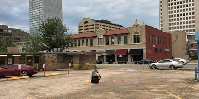 An investigator collects evidence near an Arkansas nightclub where police say multiple people were shot, Saturday, July 1, 2017, in Little Rock, Ark. (AP Photo/Andrew DeMillo)