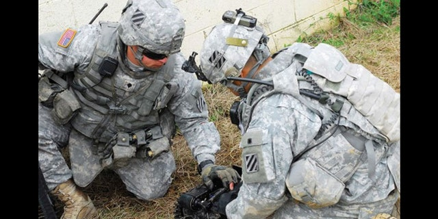 Two Soldiers prepare a robot for a mission as part of an experiment at Fort Benning, Ga.
