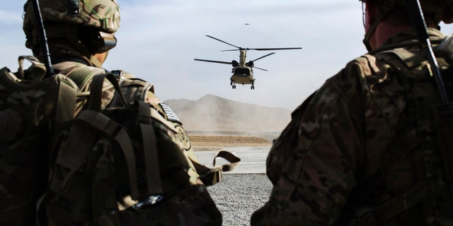File photo - U.S. soldiers from the 3rd Cavalry Regiment watch as CH-47 Chinook helicopter from the 82nd Combat Aviation Brigade lands after an advising mission at the Afghan National Army headquarters for the 203rd Corps in the Paktia province of Afghanistan December 21, 2014.