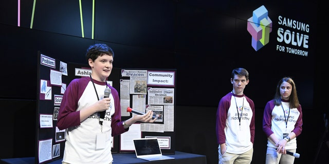 From left, students Isaac Campbell, Caleb Campbell and Aubree Hay from Ashland Middle School present their Solve for Tomorrow last year in New York.