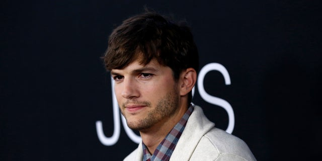 "August 13, 2013. Cast member Ashton Kutcher poses at the premiere of ""Jobs,"" in Los Angeles, California."