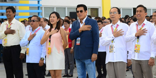 In this handout photo provided by the Tanuan City Information Office, Tanauan city Mayor Antonio Halili, third from right, attends a flag raising ceremony minutes before he was shot outside the municipal hall.