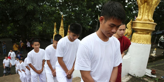 Soccer coach Ekkapol Chantawong, front, and members of the rescued soccer team arrive to attend a Buddhist ceremony that is believed to extend the lives of its attendees as well as ridding them of dangers and misfortunes, in Mae Sai district, Chiang Rai province, northern Thailand.