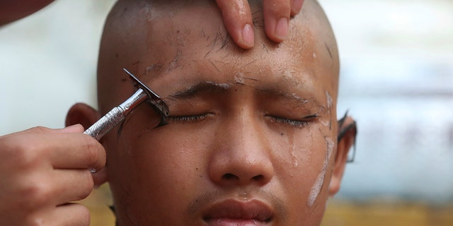 Soccer team member Pipat Pho, his coach, and teammates who were rescued last week from a flooded cave have their heads shaved in a traditional Buddhist ceremony.