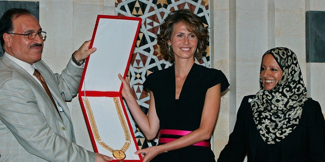 August 27, 2008: Karim Farman, Chairman of Paris-Based Arab Woman Studies Center, left, and member Shakour Al-Ghomari, right, give Syria's first lady Asma Assad the Center's prize of the Arab First Lady of 2008, in Damascus. The prize was awarded to Assad for her role in sponsoring National projects aimed at enhancing education and development in rural areas in Syria.