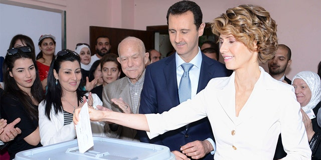 June 13, 2014: Syria's President Bashar Assad and his wife Asma cast their votes in the country's presidential elections at a polling station in Damascus.