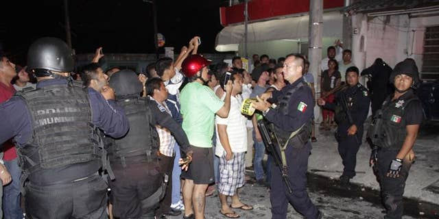 Police in Cancun restrain an angry mob that attacked Ukrainian citizen Aleksey Makeev (not pictured), who became notorious for filming himself shouting insults at Mexicans and uploading the videos to YouTube.