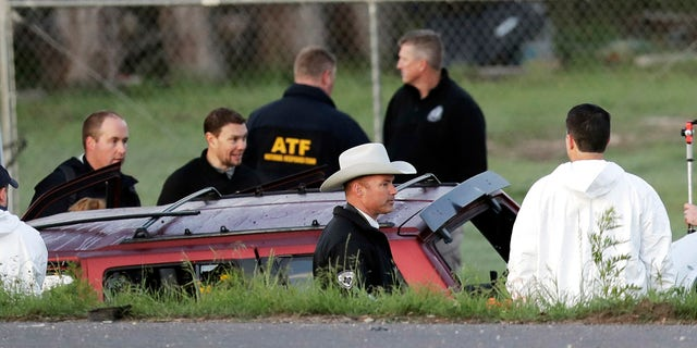 Officials investigate the scene where a suspect in a series of bombing attacks in Austin blew himself up as authorities closed in, Wednesday, March 21, 2018, in Round Rock, Texas.