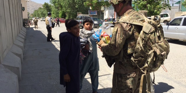 Major Jared Auchey with street children outside U.S. base in Kabul
