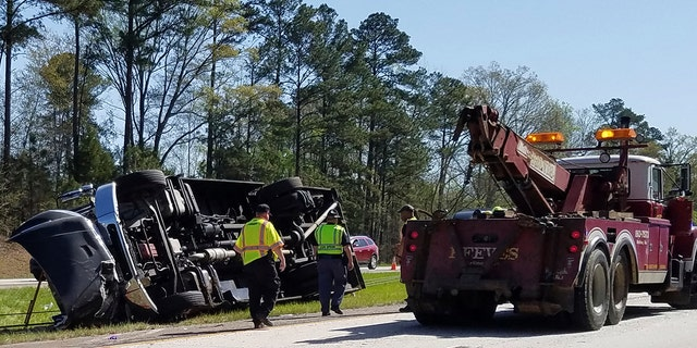 Police officers and emergency workers examine the scene of the accident scene Thursday morning, April 5, 2018.