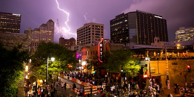 Lightning streaks across the sky over 6th Street during South by Southwest festival on Friday, March 18, 2016, in Austin, Texas. (Jay Janner/Austin American-Statesman via AP)