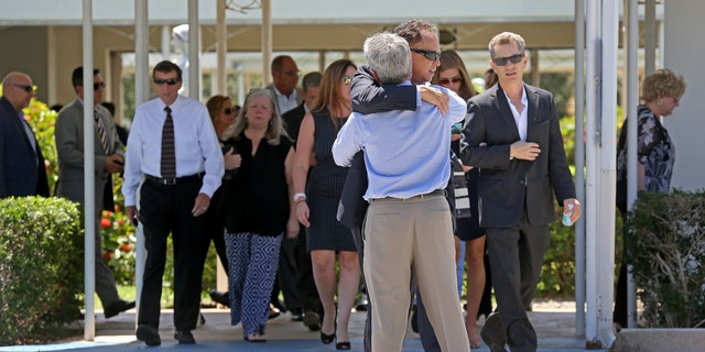 Mourners exit the Parker Playhouse following a memorial service for John Stevens and his wife Michelle Mishcon, Friday, Aug. 19, 2016, in Fort Lauderdale, Fla. A Florida sheriff's office said Friday, that Austin Harrouff, 19, will be charged with two counts of first-degree murder in the couples death, raising the possibility of the death penalty.