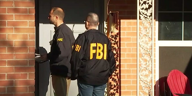 FBI agents can be seen in an Austin neighborhood after an explosion at a home left a teenager dead and a woman injured.
