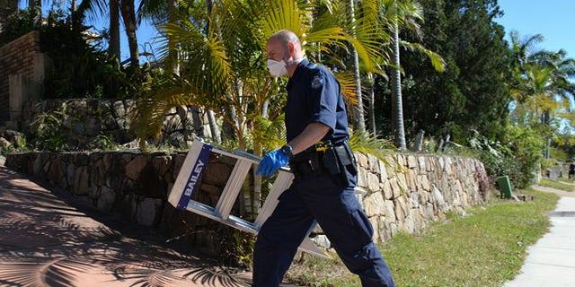 Sept. 18, 2014: A police officer searches a house in Mount Gravatt, Brisbane, Australia