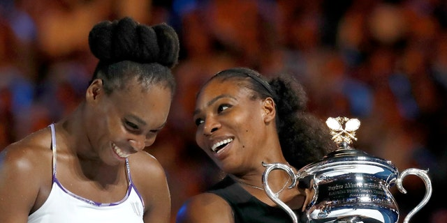 United States' Serena Williams, right, and her sister Venus chat, holding their trophies after Serena won the women's singles final at the Australian Open tennis championships in Melbourne, Australia, Saturday, Jan. 28, 2017. (AP Photo/Kin Cheung)