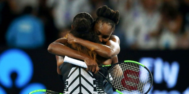 United States' Venus Williams, rear, embraces her sister Serena after Serena won the women's singles final at the Australian Open tennis championships in Melbourne, Australia, Saturday, Jan. 28, 2017. (Jack Thomas/Pool via AP)