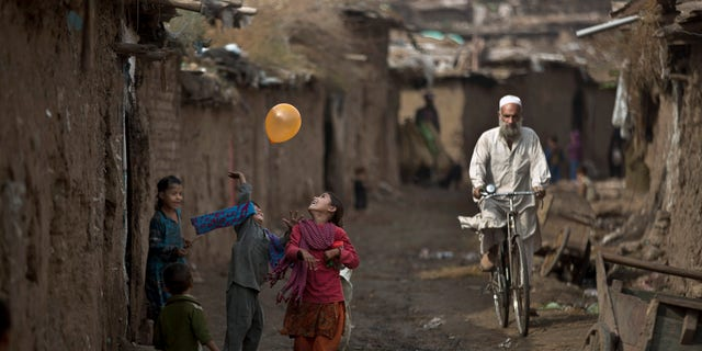 Afghan refugee children play with a balloon in an alley of a poor neighborhood on the outskirts of Islamabad, Pakistan, Thursday, Oct. 31, 2013. Pakistan hosts over 1.6 million registered Afghans, the largest and most protracted refugee population in the world, according to the U.N. refugee agency, thousands of them still live without electricity, running water and other basic services. (AP Photo/Muhammed Muheisen)