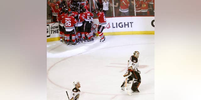 Anaheim Ducks goalie Frederik Andersen (31) and teammate Cam Fowler (4) skate off the ice as the Chicago Blackhawks celebrate their 5-4 win during the second overtime in Game 4 of the Western Conference finals of the NHL hockey Stanley Cup playoffs, Saturday, May 23, 2015, in Chicago. (AP Photo/Charles Rex Arbogast)