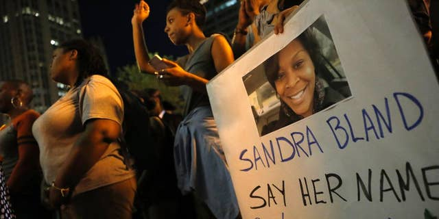 A demonstrator holds a Sandra Bland sign during a vigil, Tuesday evening, July 28, 2015,  near the DuSable Bridge on Michigan Ave. in Chicago. Bland died in a Texas county jail after the traffic stop for failing to use a turn signal escalated into a physical confrontation. Authorities have said Bland hanged herself, a finding her family disputes. The death has garnered national attention amid increased scrutiny of police treatment of blacks in the wake of several high-profile police-involved deaths. (AP Photo/Christian K. Lee)