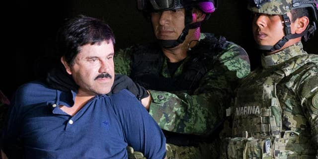 """In this Jan. 8, 2016 file photo, a handcuffed Joaquin """"El Chapo"""" Guzman is made to face the press as he is escorted to a helicopter by Mexican soldiers and marines at a federal hangar in Mexico City."""