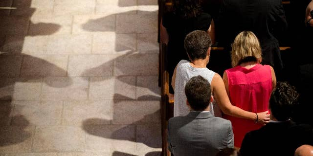 Mourners pray during the funeral service for Christopher Leinonen at the Cathedral Church of St. Luke in Orlando.