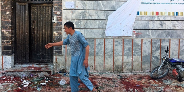 An Afghan man walks outside a voter registration center, which was attacked by a suicide bomber in Kabul, Sunday, April 22, 2018.