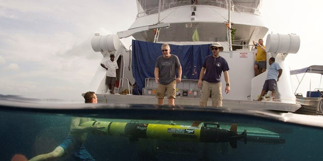 Members of the Project Recover team retrieve a REMUS 100 Autonomous Underwater Vehicle from the water's of Hansa Bay Papua New Guinea (Project Recover)