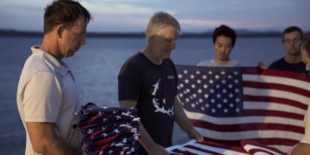 """Eric Terrill, co-founder of Project Recover and an oceanographer from Scripps Institution of Oceanography at the University of California San Diego, holds a stack of American flags commemorating the 11 crew members loss when """"Heaven Can Wait"""" crashed. The Project Recover team conducts a commemorative flag folding ceremony at the location of each crash site they discover. (Project Recover)"""