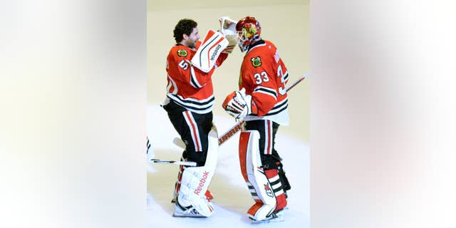 Chicago Blackhawks goalie Corey Crawford, left, congratulates teammate Scott Darling on his 35-save victory over the Nashville Predators in Game 3 of the Western Conference first-round NHL Stanley Cup Playoff series at the United Center in Chicago on Sunday, April 19, 2015. The Blackhawks lead the series 2-1. ( John Starks/Daily Herald via AP) MANDATORY CREDIT; MAGS OUT