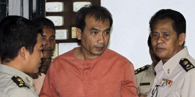 December 8, 2011: Joe Gordon, a Thai-born American, center, is escorted by correction officials at a criminal court in Bangkok, Thailand.